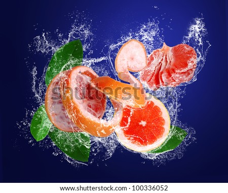 Grapefruit with peeled skin, leaves and segments in water drops on the dark blue background - stock photo