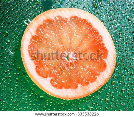 Grapefruit with water drops isolated on green background. - stock photo