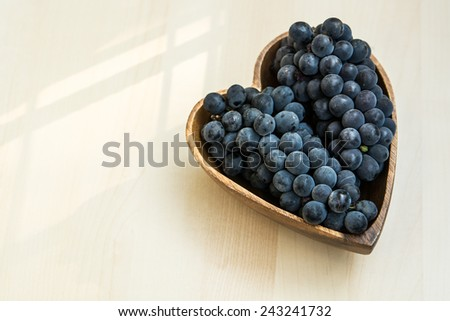 Grapes in a heart shape wooden plate, close up - stock photo