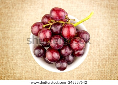 Grapes in bowl on hessian burlap background - stock photo