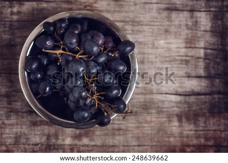 Grapes on old wooden surface. Shallow depth of field, toned photo. - stock photo