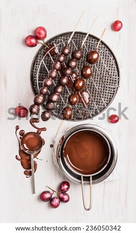 Grapes with chocolate glaze on skewers, preparation on white wooden background , top view - stock photo