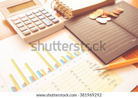 graph and note book on the wooden table with vintage color concept - stock photo