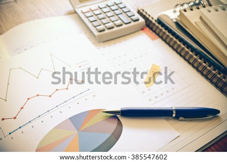 graph and note book on the wooden table with vintage color concept