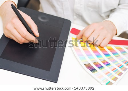 Graphic design, printing, advertising Graphic designer working with digitizer and pantone palette - stock photo