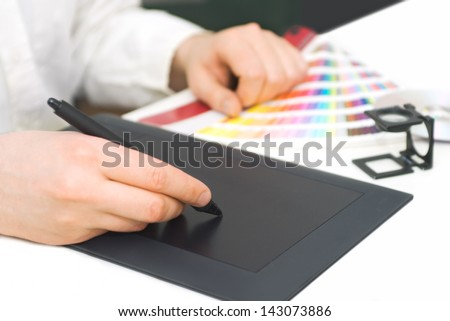 Graphic design, printing, advertising Graphic designer working with digitizer, magnifier, pantone palette
