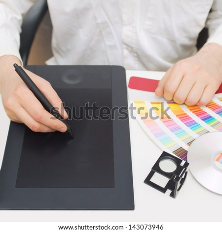 Graphic design, printing, advertising Graphic designer working with digitizer, magnifier, pantone palette, dvd - stock photo