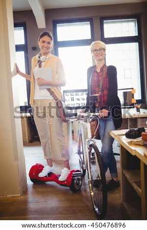 Graphic designer holding bicycle while colleague standing on hover board in office - stock photo
