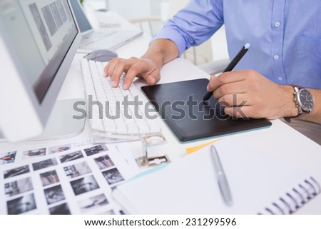 Graphic designer using digitizer at his desk in creative office - stock photo
