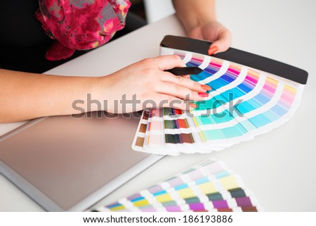 Graphic designer working on a digital tablet with a color palette - stock photo