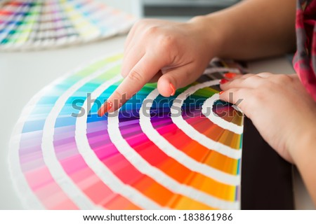 Graphic designer working with pantone palette in studio - stock photo