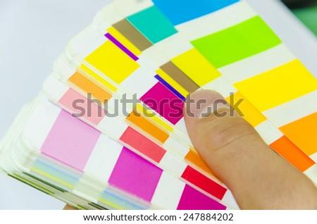 Graphic designer working with pantone palette in studio - stock photo
