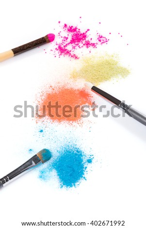 Graphic High Angle Still Life of Colorful and Vibrant Powder Eyeshadows in Pink, Yellow, Orange and Blue with Applicator Brushes on White Background with Copy Space