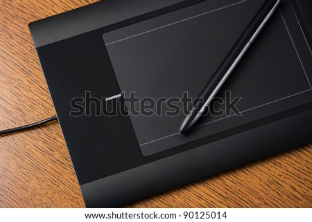 Graphic tablet on wooden table with digital pen - stock photo