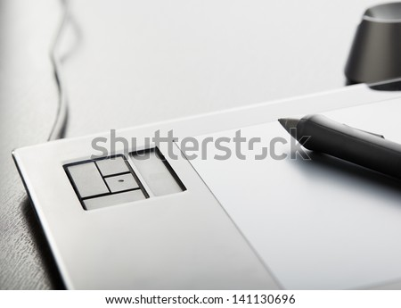 Graphic tablet with pen on table - stock photo