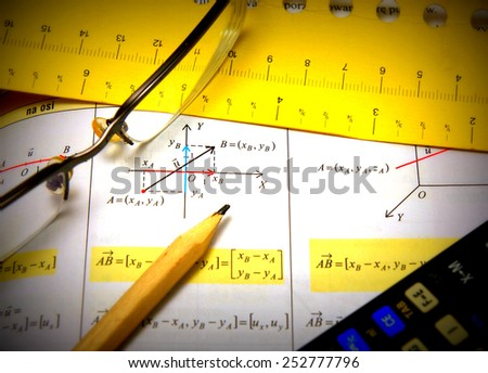 Graphs and charts of vectors (vector) theory together with glasses, calculator and wood pencil - central focus - stock photo