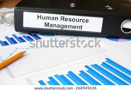 Graphs and file folder with label Human Resource Management. Business concept. - stock photo