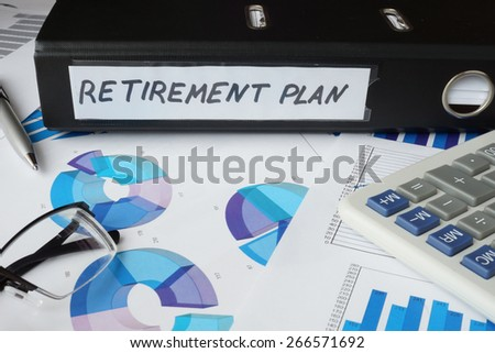 Graphs and file folder with label retirement plan. Business concept. - stock photo