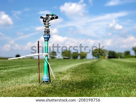 grass garden spring sprinkle water in a row  - stock photo