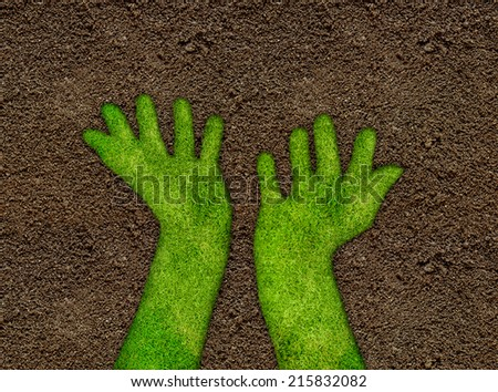 Grass hands on soil background - stock photo