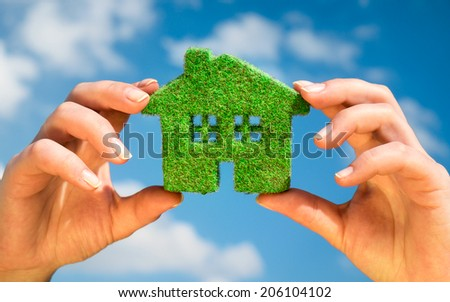 Grass home on a background of blue sky in human hands. Eco Concept. - stock photo