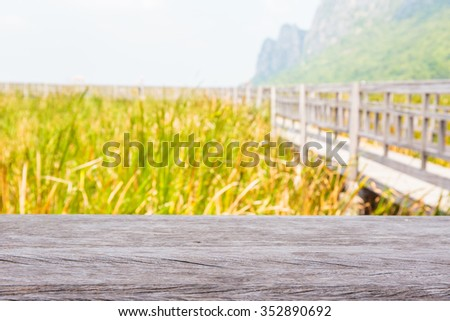 Grass in lake and mountain background with wooden plank. - stock photo