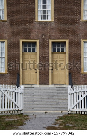 Grass-lined pathway and opened white picket fence gate leading to steps and two yellow antique doors.