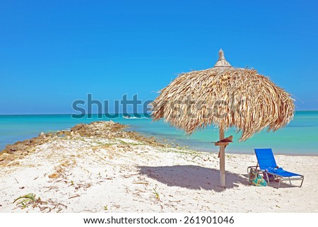 Grass umbrella at the beach on Aruba in the Caribbean - stock photo