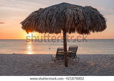 Grass umbrellas at the beach on Aruba island at sunset - stock photo
