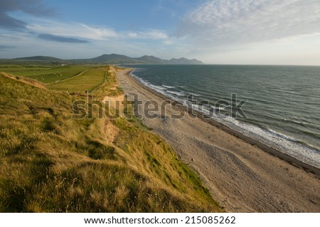 Grasses blowing in the wind lead to green farm land and sand banks in the evening sun with a pebble and sand beach leading to mountains. Dinas Dinlle, Wales coast path, Gwynedd, Wales, UK - stock photo