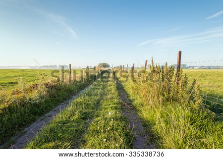 Grassland intersected by a narrow path with on both sides a fence from wooden posts and barbed wire. At the end of the path is blurred a church visible.