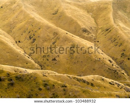 Grassland on folded eroded mountain slope turned dry and yellow by drought - stock photo