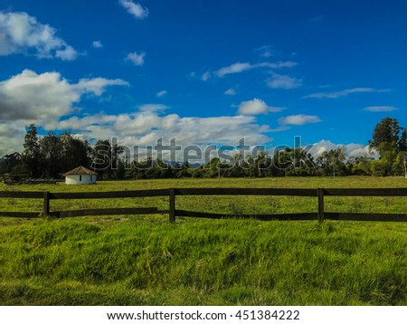 Grassland with a fence in a blue sky day - stock photo