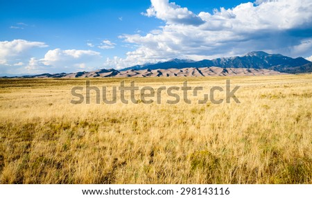 Grassy Plain with Mountain Range at Great Sand Dunes National Park - stock photo