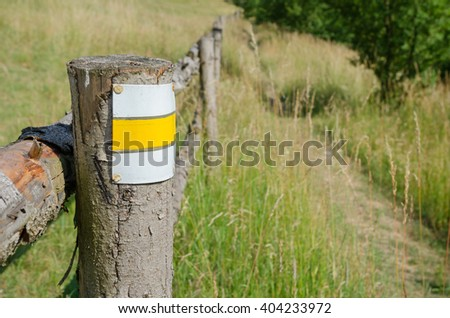 Grassy rural landscape with tourist mark on the pole - stock photo