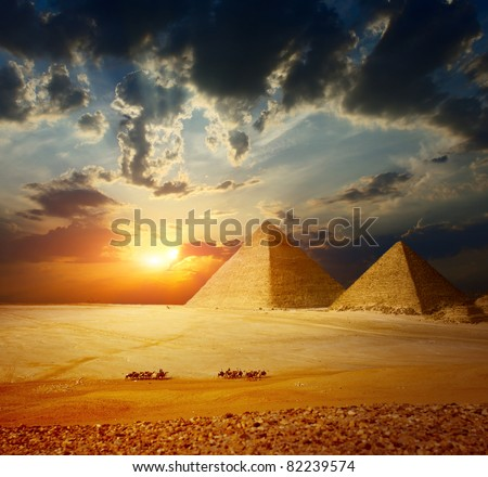 Grate pyramids in Giza valley in Egypt with group of bedouins on camels riding through desert - stock photo