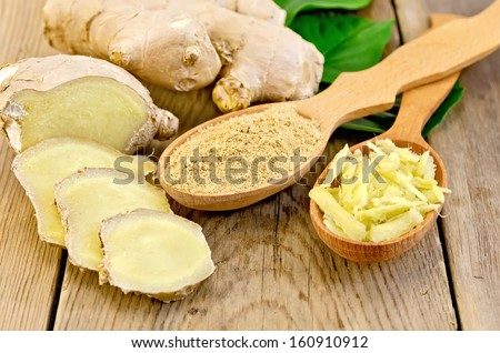 Grated and ground ginger in two wooden spoons, ginger root, green leaves on the wooden board - stock photo