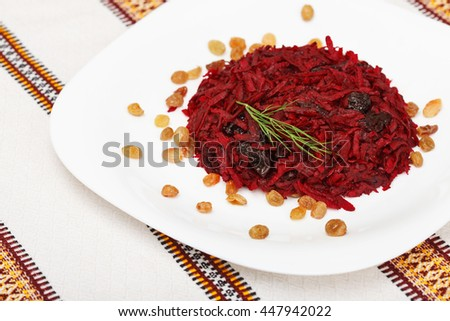 Grated beet salad with prunes and raisins, served on a white plate and home tablecloth - stock photo
