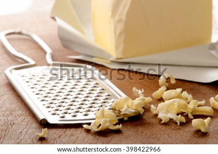 grated butter and grater on wooden board - stock photo