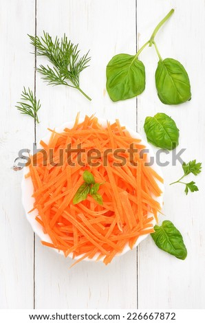 Grated carrot in bowl and herbs on white wooden table, top view - stock photo