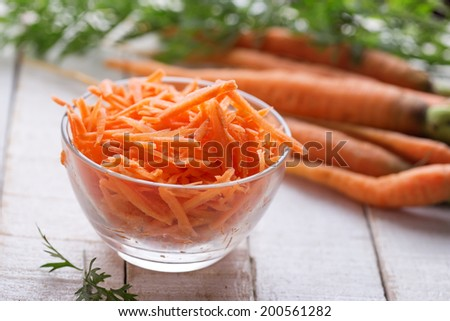 Grated carrots in bowl  on white table. Selective focus. - stock photo