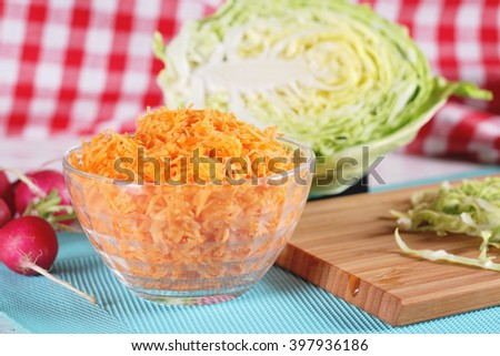 Grated carrots in the vessel and other healthy diet food menu ingredients closeup. Salad of carrot, radish and cabbage cooking. - stock photo
