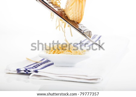 Grated cheese falling into white bowl on towel isolated on white background. - stock photo