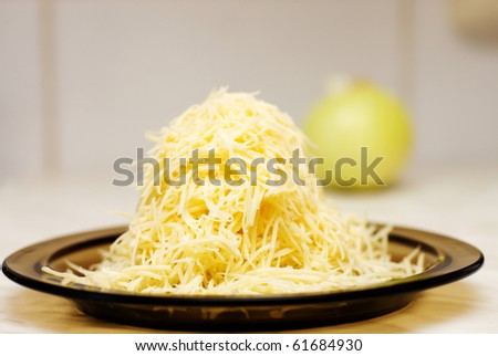 grated cheese on plate on kitchen table - stock photo