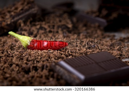 Grated Chocolate with Red Chilli Pepper on wooden background closeup - stock photo