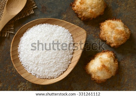 Grated coconut on small plate with coconut macaroons on slate, photographed overhead with natural light (Selective Focus, Focus on the grated coconut and the top of the macaroons) - stock photo