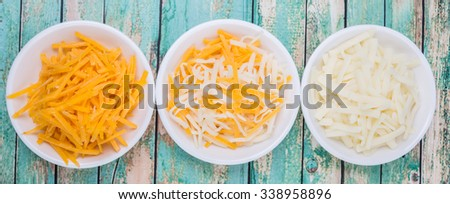 Grated mix mozzarella and cheddar cheese in white bowls over wooden background - stock photo