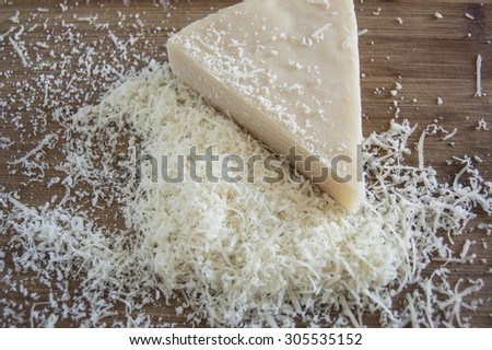 Grated Parmesan cheese on wooden board - stock photo