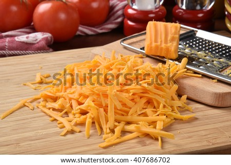 Grated sharp cheddar cheese with tomatoes in the background - stock photo