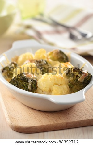 Gratin with cauliflower, broccoli and cheese in a baking dish - stock photo